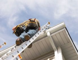 worker on ladder repairing eavestrough